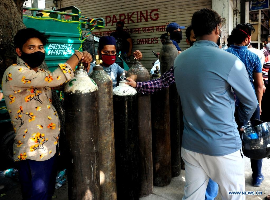 People wait in line to refill empty medical oxygen cylinders for COVID-19 patients in front of a shop in New Delhi, India, April 26, 2021.