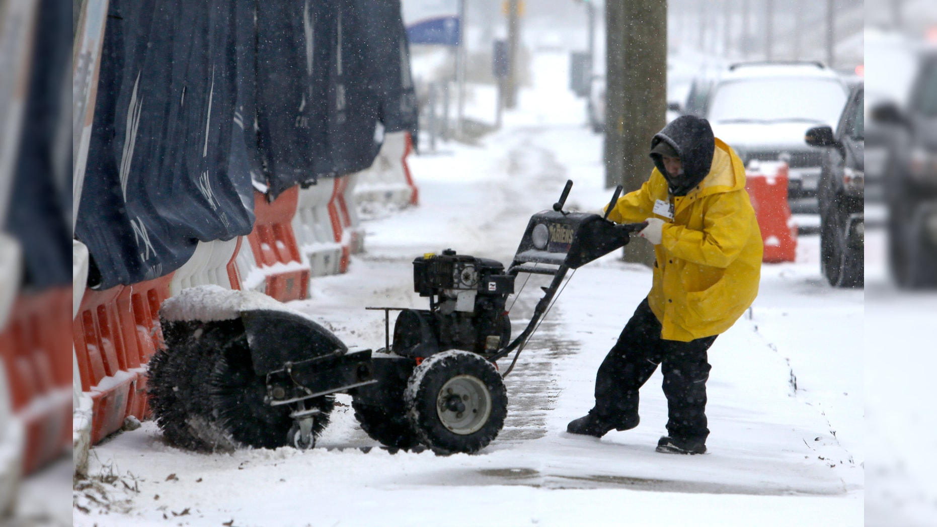 A man works to turn his snow-clearing machine on Sunday in Philadelphia. After days of frigid temperatures, the Northeast is being hit with a whopper of a storm that could dump well over a foot of snow in many areas and create blizzard-like conditions. (AP)