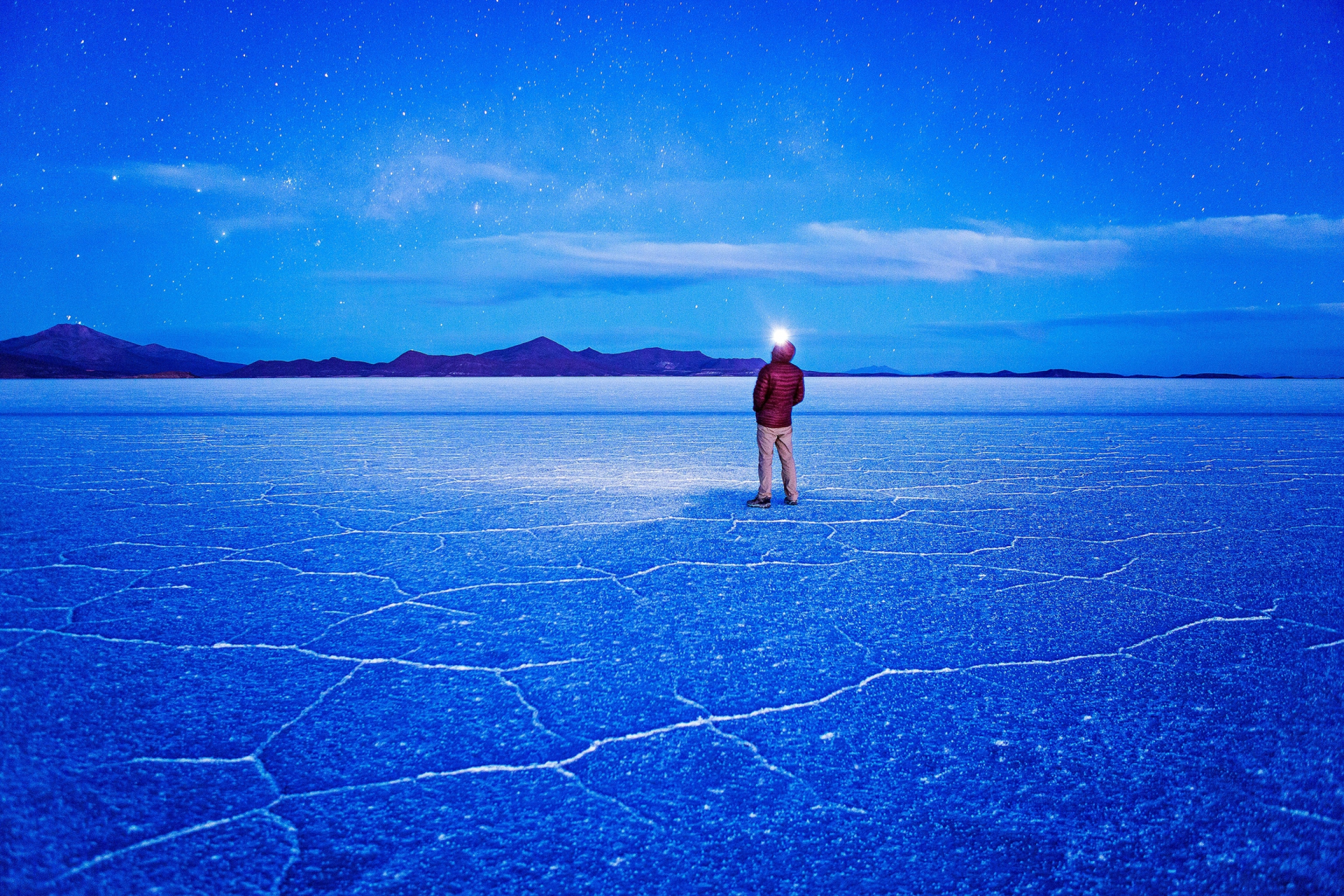 The star-studded night sky casts the salt flats shades of blue. During the dry season the ground hardens and polygonal patterns of salt rise from the ground. PHOTOGRAPH BY ERIC HANSON, GETTY IMAGES